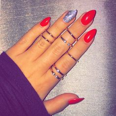 Red stiletto nails with silver glitter accent paired with 14k gold rings