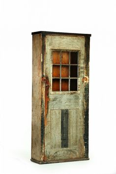 """DECORATED CUPBOARD.  Attributed to Deerfield, Massachusetts, 18th century, pine. One-piece cupboard with a nine-pane door over a double-paneled door, and old blue and white paint. 79.5""""h. 35.5""""w. 13""""d."""