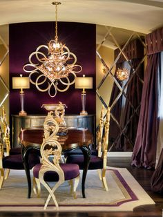 This striking dining room is designed in shades of purple and gold, with an ornate chandelier and dining chairs. A wall of mirrors in a diamond pattern reflects the purple and gold colors to create depth in the space. A neutral area rug anchors the space and brightens the room with a lighter color.