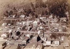 The picture shows Section of small city showing residential  and commercial buildings; trees and mountains in  background. It was taken in 1887 by Grabill, John C. H.,  photographer