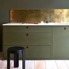 This lustrous splashback, made from brass that's been tarnished using chemicals, was created by British brand Naked Kitchens (nakedkitchens.com). The 'Invisible Green' paint by Little Greene, shown here on the walls and units ( littlegreene.com), allows the splashback wall to shine.