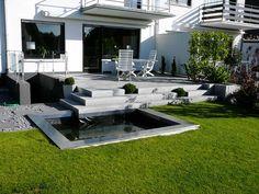 Moderne Steinterrasse und Gartenteich