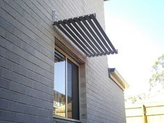 Aluminium powdercoated window awning with slats in Woodland Grey®