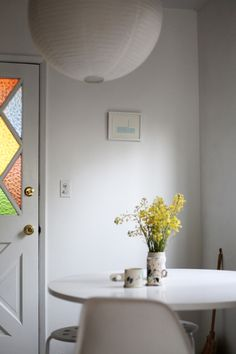 """Sneak Peek: Claire Cottrell. """"A linoleum block print by Cortney Cassidy, my handmade broom and the stained glass door to my backyard. It makes a rainbow on my walls every day between 4 and 5 pm."""" #sneakpeek"""