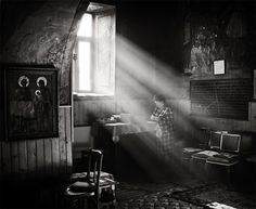 The strong beam of sunlight shining through the window illuminates the dark interior of the woman's house.  I always associate light with warmth and comfort, so I love that the woman is sitting directly in the sun's beam.  It gives the picture the appearance of being hopeful instead of depressing.
