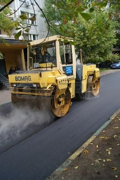 12201094 Packing of a new asphalt covering on road before an apartment house within the limits of the city program of an accomplishment of domestic territories, on september 30, 2011, in Moscow.