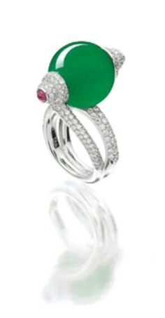 Centring on a good translucent jadeite bead of emerald green colour, flanked by a cabochon ruby, decorated with brilliant-cut diamonds to the shoulders, the diamonds together weighing approximately 1.90 carats, mounted in 18 karat white gold.