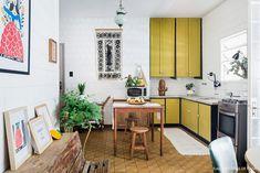 Cozinha com lajotas antigas, tapeçaria na parede, armários amarelos e mesa de madeira.