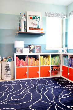 Bookshelves organized by color in a shared bedroom for animal-loving little boys. Bunk beds, bookshelves, toy storage, and vintage travel posters complete this safari-themed shared boys' bedroom. Kids' rooms should be colorful, fun, and easy to keep organized.