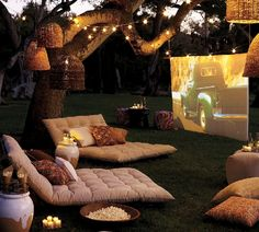 Summertime Outdoor Movie Theater made with a taunt sheet, projector, twinkle lights, popcorn & treats, comfortable seating, and an old oak tree if you have one! Easy to set up and take down.