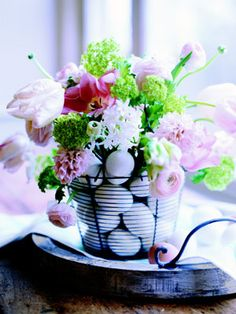 Streamline your decorating by combining undyed eggs and a casual bouquet in a single, simple arrangement. The key: a minimalist wire basket reminiscent of the kind used to gather eggs in henhouses. Inside, set a clear glass cylinder vase filled with a loose bunch of tulips, lilacs, and ranunculus. Hard-boil or blow out two dozen eggs, and nestle around the vase.%0A - GoodHousekeeping.com