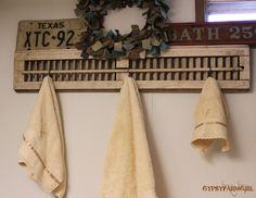 Towel holder from old shutter and S hooks. I also love the license plate and old scale as candle holder.