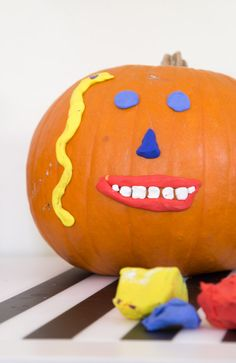 Use modeling clay to make 3D faces on pumpkins! (Plus click through for 11 more kids pumpkin decorating ideas that fun for all ages, look great, and last a long time.)