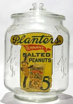 country store, America, A Planters Peanuts Mr. Peanut 8-Sided T label glass display jar. 1920s to 1930s. 8-sided display jar with T label on 8th side. Original octagon lid, original base marked made in the USA.