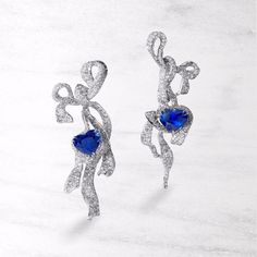 CINDY CHAO Art Jewel. Two heart-shaped sapphires are embraced by flowing diamond ribbons, together representing a delightful encounter of breeze and gems. A harmonious juxtaposition of the inherently tough qualities of the stones and the soft gestural movement of the ribbon.