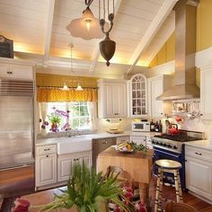 Yellow kitchen with high ceiling, apron sink, free-standing butcher block island and blue & red accents.