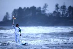 Raphael Bruhwiler surfs with the Olympic torch on Long Beach in Pacific Rim National Park located near Tofino, BC.