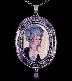 This is not contemporary - image from a gallery of vintage and/or antique objects. GEORGE HUNT (1892-1960)  A silver locket, pendant, with central enamel portrait of Lady Mackintosh,  set in a frame with silver wirework, garnets, beads, with a bead drop.