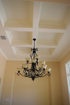Elegant Chandelier with Coffered Ceiling and Molding.