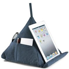 Levenger Canvas Pyramid Pillow -  One side has a rolled edge at the bottom for propping your iPad, e-reader, tablet or book. Includes a cleaning cloth for your screen. Offers several pockets all around to hold pens, notepads, phone, remote and small journal. Slide your reading glasses through the loop to keep them...