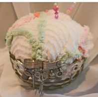 Banana Boat Vintage Glass Pincushion Measures 7 W x 11 long. A charming recycled chenille bedspread cushion framed with lace and pink ribbon woven thru; a vintage jewelry piece added. $15.00
