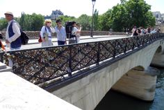 In this photo you can see the Pont de l'Archeveche bridge in Paris, showing a couple and tourists enjoying the view as well as the two love lock covered railings of the bridge which spans over the River Seine.  To see more go to www.eutouring.com/images_paris.html