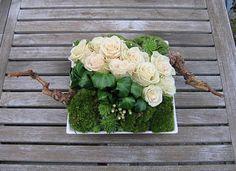 Rustiek opgemaakte schaal met rozen en mos