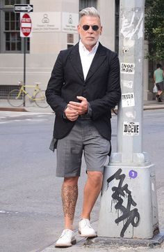 The Woost wearing a black fitted blazer with grey shorts and circle glasses.