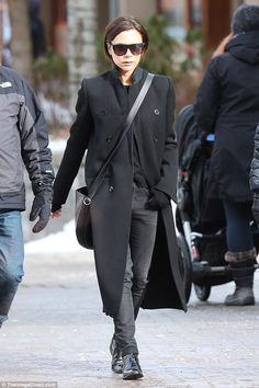 Sartorially chic: Victoria put on her signature style display for the outing - ensuring to wrap up against the chillier climes with a chic black jacket with large round buttons