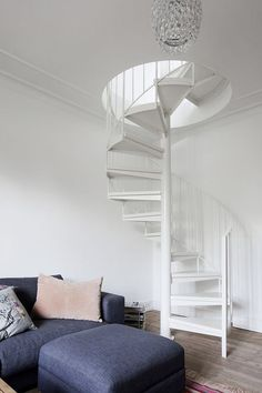 An elegant staircase in a city apartment. Chandelier hanging from the ceiling gives the place a very fancy look.