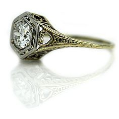 This stunning art deco engagement ring features a glittering, bright white old european cut diamond weighing approximately .75 carat accompanied by an AGI diamond report stating F color and VS2 clarity. This vintage diamond resides in a two tier hexagonal frame.   This romantic art deco ring was crafted in the 1930s in 14 kt two tone gold, and is completed with a beautiful art deco open work design. They just dont come any finer! This ring is in excellent condition and is easy to wear as it…