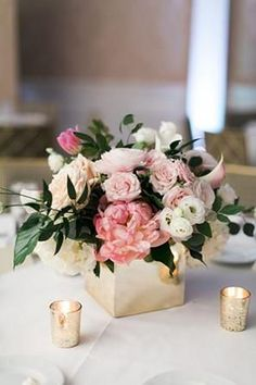 Low Wedding Centerpieces: Keep it classic with traditional flower arrangements in low vases. These pastel pink peonies and roses in a box vase blend well with gold candles for a spring or summer wedding. Square Vase Centerpieces, Peonies Wedding Centerpieces, Rose Gold Centerpiece, Wedding Table Flowers, Pastel Wedding Centerpieces, Small Wedding Centerpieces, Summer Flower Centerpieces, Gold Vases, Summer Wedding Flowers