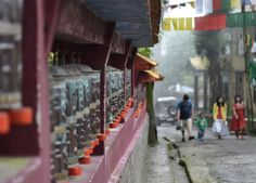 Gangtok locals come to pray walking between the prayer wheels and prayer flags en route to Enchey Monastery Gangtok. Unique Tibetan Buddhist Monastery and culture at Enchey Monastery Gangtok, Sikkim Tibetan Monasteries. Travel in Gangtok in the Sikkim Himalayan Region of India. For more on Enchey Monastery and travel in India and Southeast Asia check our blog; http://live-less-ordinary.com/southeast-asia-travel/enchey-monastery-gangtok-sikkim