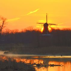 De Zwaan (The Swan) windmill located on Holland's Windmill Island. Is shown with the rising sun directly behind the windmill as the sky is reflected on Black River. This is another twice a year graphic that depends on mother nature's cooperation
