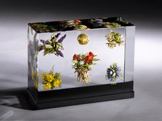 Paul J. Stankard, Golden Orb, Floral Clusters and Figures Triptych 2011, H. 6.0 x L. 8 1/8 x W. 3.0 inches, Colored glass encased in clear glass, cut, polished and laminated Photo Credit - Ron Farina