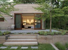 bardage bois massif, portes coulissantes, baies vitrées, sol en pierre grise et allée de jardin en pas japonais