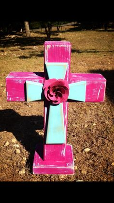 Hot pink and turquoise wooden cross. Stands 19 inches tall.