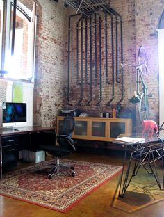 the brick, the piping, the hanging bike, the Mac, the windows...this may just be the best home office ever (from an old rubber factory boiler room that has been converted into an impressive living area)