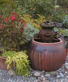 Note the ground covered in gravel with small rocks for accents around the pots. I like this much better than dirt. Garden Fountains, Garden Statues, Water Fountains, Rock Fountain, Strawberry Planters, Garden Whimsy, Water Features In The Garden, Outdoor Living, Outdoor Decor