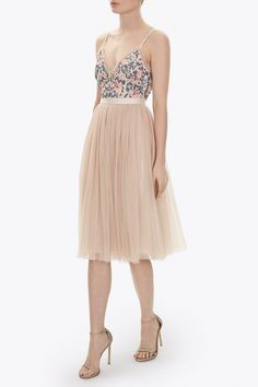 The petal pink Whisper Midi Dress consists of a fitted bodice with a flattering camisole neckline and a voluminous layered tulle skirt. The bodice is detailed with tulle frill trims and a dusty pink and blue floral artwork inspired by Victorian whitework fabric embroidery. The dress is finished with a signature Needle & Thread grosgrain trim at the waistband and has adjustable straps.