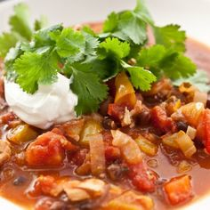Chicken Chili Recipe with yellow onion, butter, garlic, red bell pepper, yellow bell pepper, chili powder, ground cumin, red pepper flakes, cayenne pepper, kosher salt, diced tomatoes, black beans, cilantro, chicken, sour cream