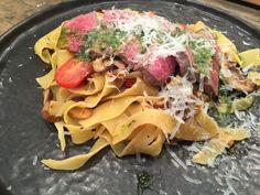 eutje olijfolie om in te bakken in een hapjespan en bak de paddenstoelen circa 8 minuten op middelhoog vuur.  •  Halveer de tomaten.   •  Pel en snijd de...