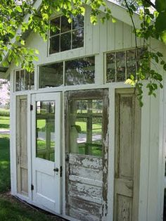 I am so in LOVE!...a garden house from recycled doors and windows... What a GREAT idea!!!  Warming shed for the girls bus stop?