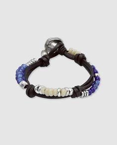 Pulsera con varias vueltas de cordón de cuero con cristales  en tonos azules y blancos, cuentas de metal bañado en plata en diferentes formas y tamaños intercaladas, y cierre de botón. Con un diseño exclusivo, original y rompedor característico de UNOde50. Esta pulsera es una joya diseñada y creada íntegramente en España de forma artesanal.
