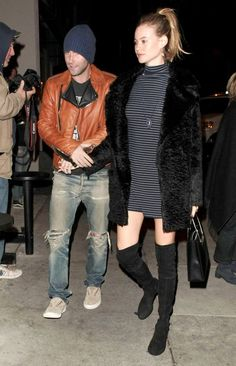 Behati Prinsloo wears a striped mini dress, faux fur coat, suede thigh-high boots, a shopper bag, and a pendant necklace