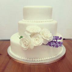 Pastel de boda blanco con rosas y lavanda hechas de azúcar