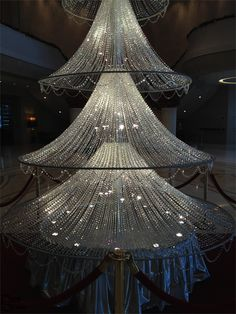 a fifteen foot crystal Christmas tree standing under a huge Swarovski crystal chandelier.in the lobby of  the hotel,Harbour Grand, in Hong Kong.