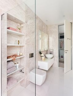 The wife's ensuite bathroom has a glamorous look with soft pink Rosa Egeo marble walls and bright white Thassos marble stone flooring. The inset storage space features opal white marble stone shelves, and the hanging vanity is uniquely detailed with a white quilted lacquered front.