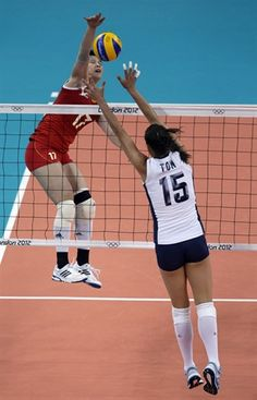 China's Zhang Lei spikes the ball over Logan Tom during a women's preliminary volleyball match at the 2012 Summer Olympics