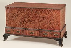 Decorated furniture: Blanket chest attributed to the Leiby School of decoration having a lid and case painted with bold salmon and black swirls, above a stepped base with three drawers with similar vertical feathering and ebonized trim, retaining its original oval brasses, all on tall ogee bracket feet. Lehigh County, Pennsylvania, circa 1815